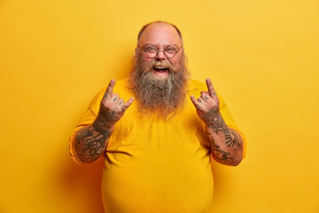 Zwaarlijvige grappige man in geel t-shirt, toont heavy metal bord, woont concert van favoriete muziekband bij, heeft dikke buik, getatoeëerde armen en baard, draagt een ronde bril. overgewicht rock fan gebaren indoor