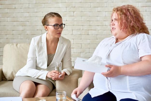 Zwaarlijvige jonge vrouw bespreken psychische problemen met vrouwelijke psychi