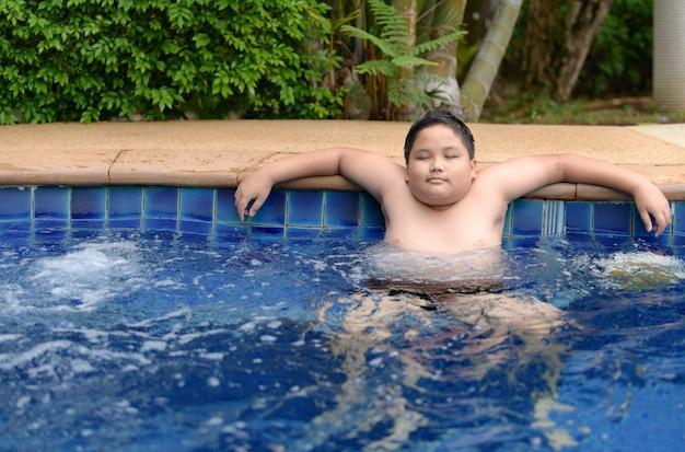Zwaarlijvige jongen ontspannen genieten van hot tub
