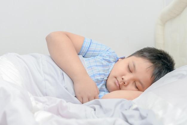 Zwaarlijvige jongensslaap op bed,