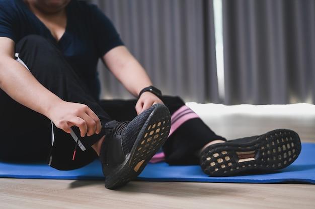 Zwaarlijvige vrouw die schoenveter bindt en zich voorbereidt op oefeningen thuis. gezondheid en wil afvallen concept.