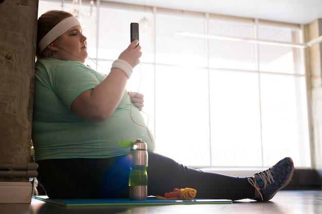 Zwaarlijvige vrouw die smartphone na training
