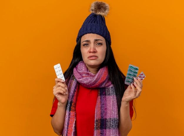 Zwak jong kaukasisch ziek meisje dat de winterhoed en sjaal draagt die pakken medische pillen houdt die op oranje muur met exemplaarruimte worden geïsoleerd