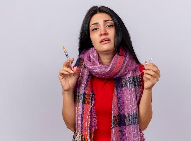 Zwak jong kaukasisch ziek meisje die de spuit en de ampul van de sjaalholding dragen die op witte muur met exemplaarruimte wordt geïsoleerd
