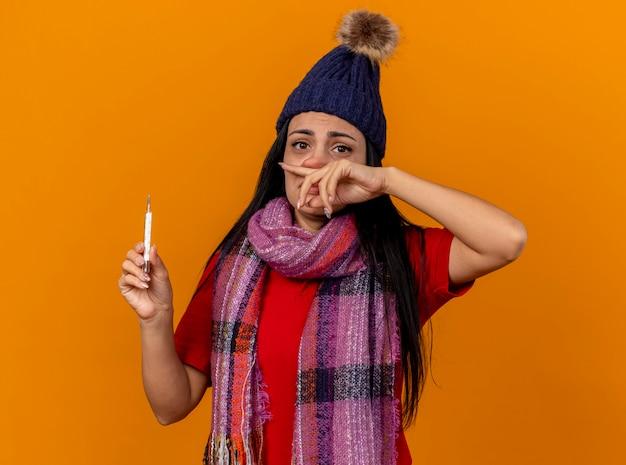 Zwak jong kaukasisch ziek meisje die de winterhoed en sjaal dragen die thermometer afvegende neus houden die op oranje muur wordt geïsoleerd