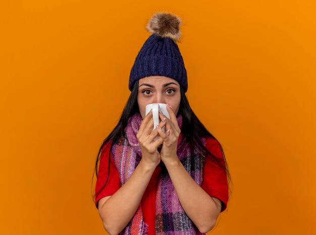Zwak jong kaukasisch ziek meisje die de wintermuts en sjaal dragen die thee drinken uit kop die op oranje muur met exemplaarruimte wordt geïsoleerd