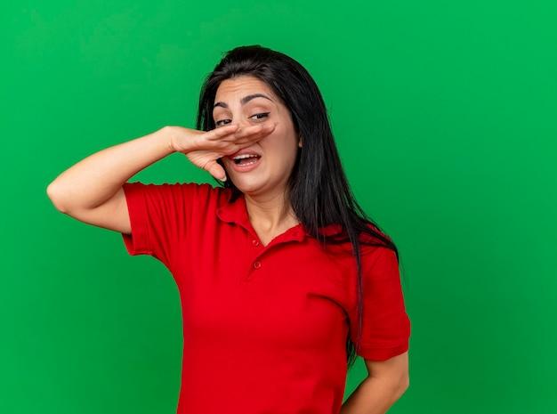 Zwak jong kaukasisch ziek meisje die kant afvegende neus met hand bekijken die op groene achtergrond met exemplaarruimte wordt geïsoleerd