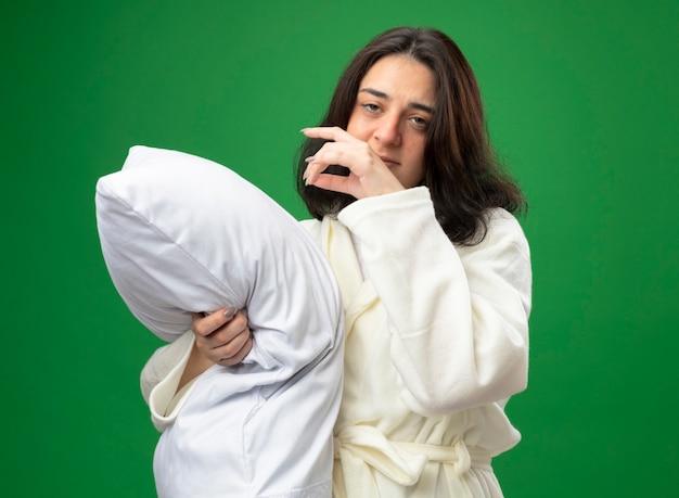 Zwak jong kaukasisch ziek meisje die kleed dragen die zich in profielmening bevinden die hoofdkussen koesteren die camera houden die hand in lucht houden die op groene achtergrond wordt geïsoleerd