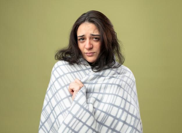 Zwak jong kaukasisch ziek meisje draagt een gewaad gewikkeld in plaid kijken camera grijpen plaid geïsoleerd op olijfgroene achtergrond met kopie ruimte
