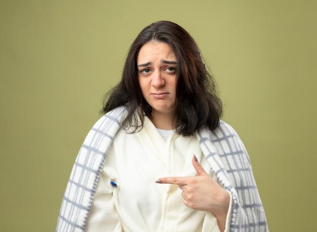 Zwak jong kaukasisch ziek meisje draagt ?? gewaad gewikkeld in plaid kijken camera houden thermometer onderarm wijzend op het geïsoleerd op olijfgroene achtergrond