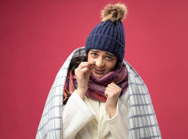 Zwak jong kaukasisch ziek meisje met gewaad winter muts en sjaal gewikkeld in plaid met vuist in de lucht aanraken van gips op neus geïsoleerd op karmozijnrode muur