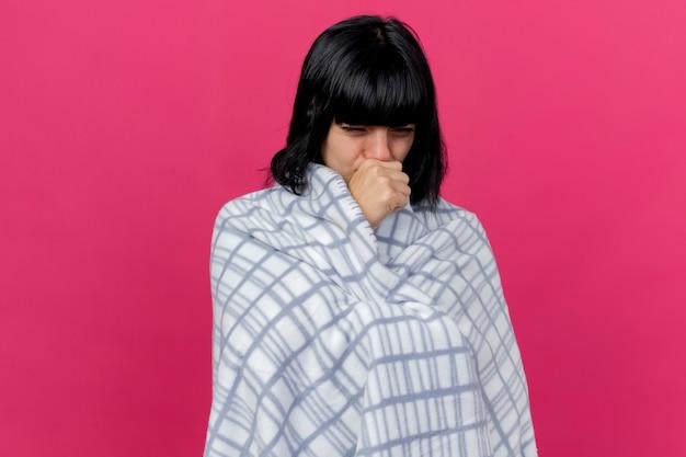 Zwak jong ziek kaukasisch meisje gewikkeld in plaid op zoek recht hoesten hand op mond houden geïsoleerd op karmozijnrode achtergrond met kopie ruimte