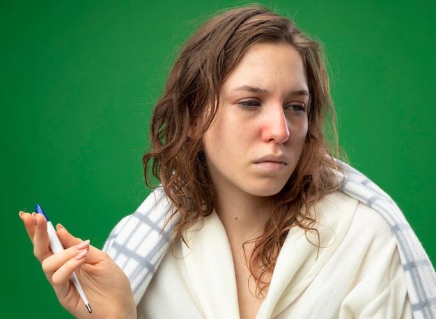 Zwak jong ziek meisje dat naar kant kijkt die wit gewaad draagt dat in de thermometer van de plaidholding wordt geïsoleerd die op groen wordt geïsoleerd