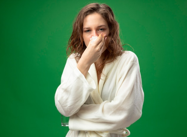 Zwak jong ziek meisje dat recht vooruit kijkt het dragen van witte gewaad afvegende neus met servet dat op groen wordt geïsoleerd