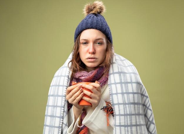 Zwak jong ziek meisje dat wit gewaad en winterhoed met sjaal draagt die in de kop van de plaidholding van thee wordt verpakt die op olijfgroen wordt geïsoleerd