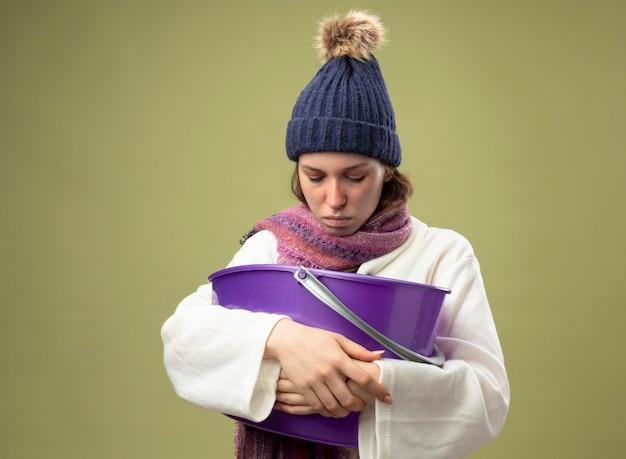 Zwak jong ziek meisje dat wit gewaad en winterhoed met sjaal draagt die plastic emmer houdt met misselijkheid die op olijfgroen wordt geïsoleerd
