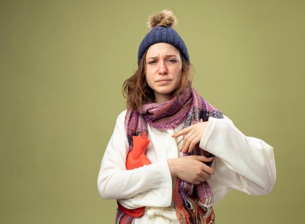 Zwak jong ziek meisje dat wit gewaad en winterhoed met sjaal draagt die warmwaterzak houdt die op olijfgroen met exemplaarruimte wordt geïsoleerd