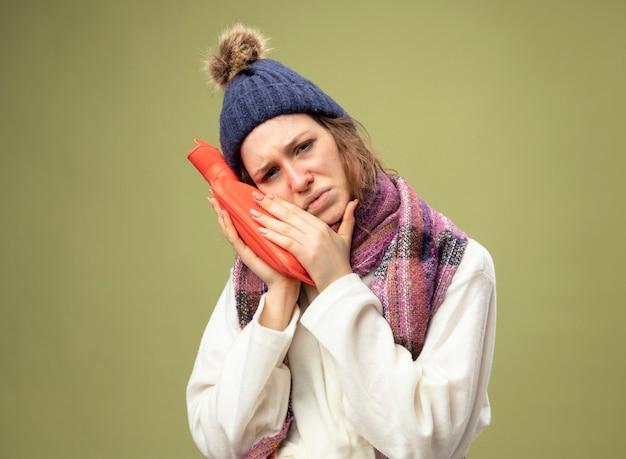 Zwak jong ziek meisje dat wit gewaad en winterhoed met sjaal draagt die warmwaterzak op wang houdt die op olijfgroen wordt geïsoleerd
