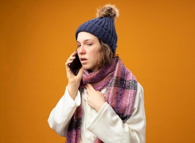 Zwak jong ziek meisje dat wit gewaad en wintermuts met sjaal draagt, spreekt over telefoon die hand op borst zet die op oranje wordt geïsoleerd