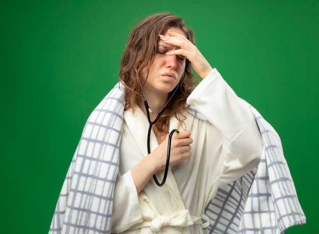 Zwak jong ziek meisje draagt een wit gewaad gewikkeld in plaid luisteren naar haar eigen hartslag met een stethoscoop en legt de hand op het voorhoofd geïsoleerd op groen