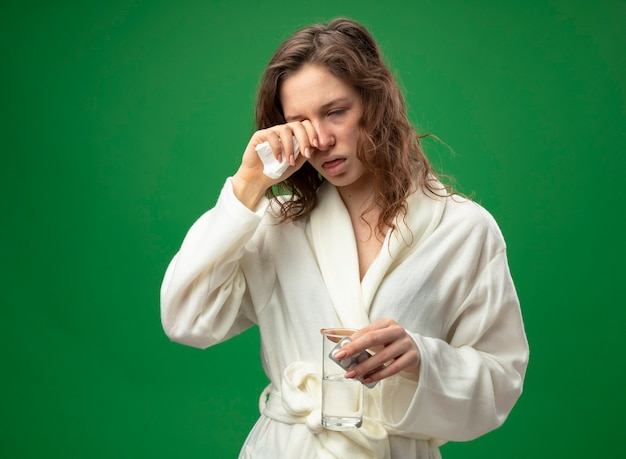 Zwak jong ziek meisje dragen wit gewaad glas water met pillen houden en afvegen oog met hand geïsoleerd op groen met kopie ruimte
