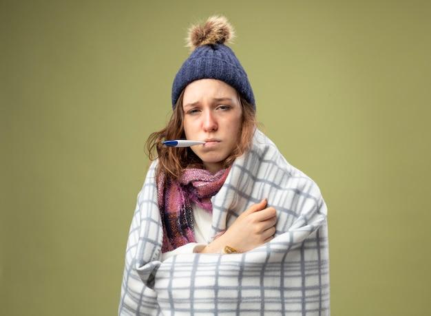 Zwak jong ziek meisje dragen witte mantel en winter hoed met sjaal gewikkeld in plaid thermometer aanbrengend mond geïsoleerd op olijfgroen