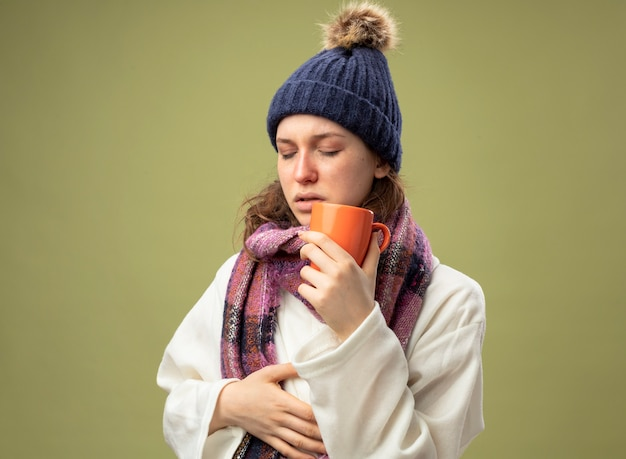 Zwak jong ziek meisje met gesloten ogen dragen witte mantel en winter hoed met sjaal houden kopje thee zetten hand op buik geïsoleerd op olijfgroen