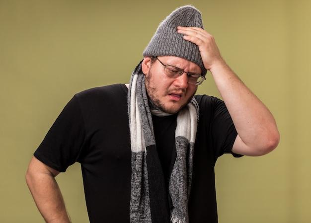 Zwak neerkijkend ziek man van middelbare leeftijd met een wintermuts en sjaal die hand op het hoofd legt