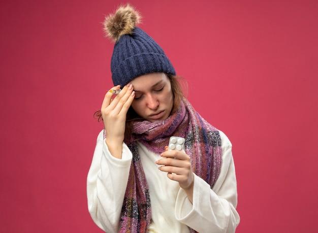 Zwak ziek meisje met gesloten ogen dragen witte mantel en winter hoed met sjaal houden pillen en spuit hand zetten voorhoofd geïsoleerd op roze