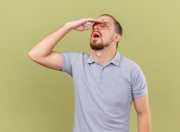 Zwakke en pijnlijke jonge knappe slavische zieke man met servet hoofd aanraken met gesloten ogen geïsoleerd op olijfgroene achtergrond