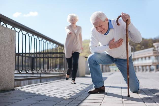 Zwakke hopeloze bejaarde man die pijn heeft en zijn hand op de borst houdt, terwijl de niet onverschillige vrouw hem te hulp schiet
