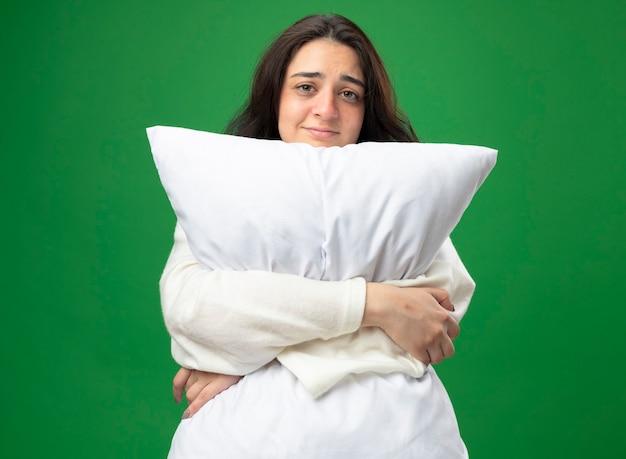Zwakke jonge blanke ziek meisje dragen gewaad knuffelen kussen kijken camera geïsoleerd op groene achtergrond