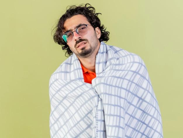 Zwakke jonge blanke zieke man met bril gewikkeld in plaid kijken camera geïsoleerd op olijfgroene achtergrond met kopie ruimte