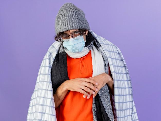 Zwakke jonge blanke zieke man met bril met masker winter muts en sjaal gewikkeld in plaid handen bij elkaar houden geïsoleerd op paarse muur