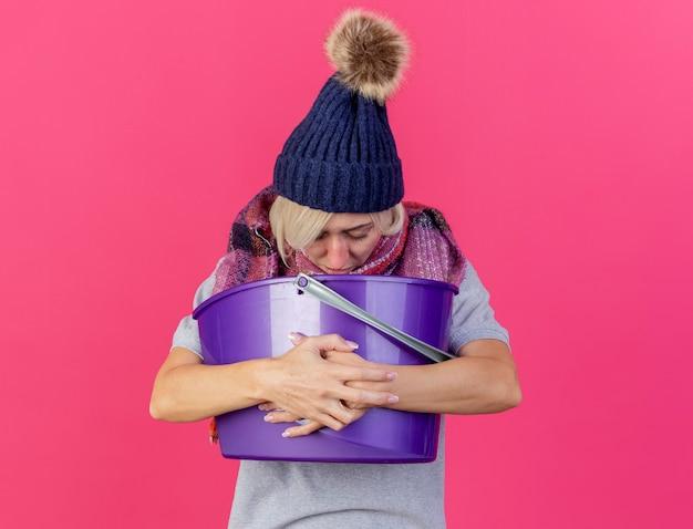 Zwakke jonge blonde zieke slavische vrouw die de wintermuts en sjaal draagt en kijkt naar plastic emmer met misselijkheid geïsoleerd op roze muur met kopie ruimte