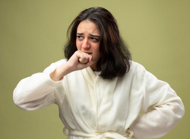 Zwakke jonge kaukasische ziek meisje dragen gewaad hoesten houden vuist in de buurt van mond kijken kant houden hand op taille geïsoleerd op olijfgroene achtergrond