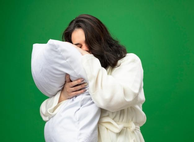 Zwakke jonge kaukasische ziek meisje dragen gewaad staande in profielweergave knuffelen kussen hoofd erop zetten met gesloten ogen geïsoleerd op groene achtergrond met kopie ruimte