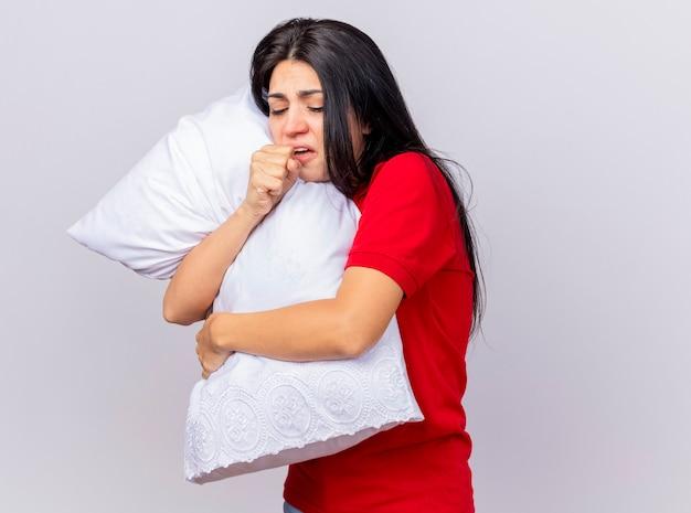 Zwakke jonge kaukasische ziek meisje permanent in profiel te bekijken knuffelen kussen hoesten met gesloten ogen vuist houden in de buurt van mond geïsoleerd op een witte achtergrond met kopie ruimte