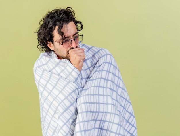 Zwakke jonge kaukasische zieke man met bril gewikkeld in plaid hoesten vuist houden in de buurt van mond met gesloten ogen geïsoleerd op olijfgroene achtergrond met kopie ruimte