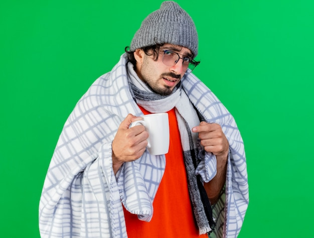 Zwakke jonge kaukasische zieke man met bril winter muts en sjaal verpakt in geruite bedrijf en wijzend op beker kijken camera geïsoleerd op groene achtergrond met kopie ruimte