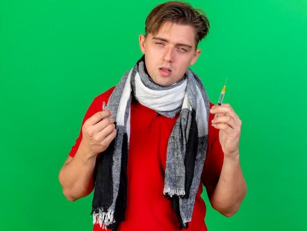 Zwakke jonge knappe blonde zieke man die sjaal draagt die spuit en medische ampul houdt die voorzijde bekijkt die op groene muur wordt geïsoleerd