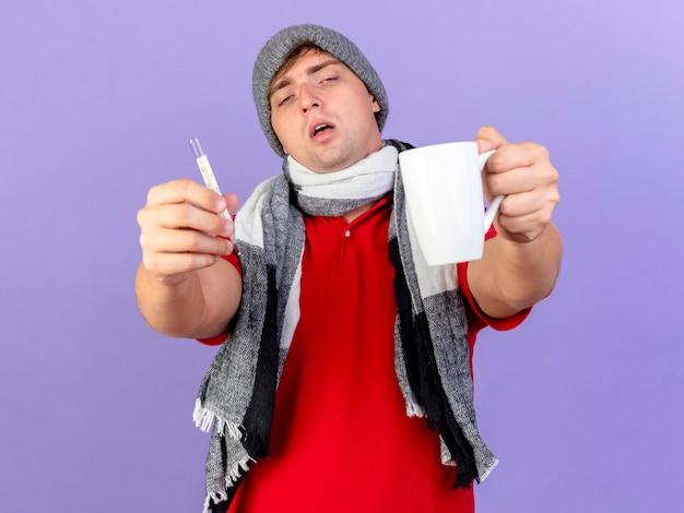 Zwakke jonge knappe blonde zieke man met muts en sjaal die thermometer en beker uitrekt naar geïsoleerd op paarse muur