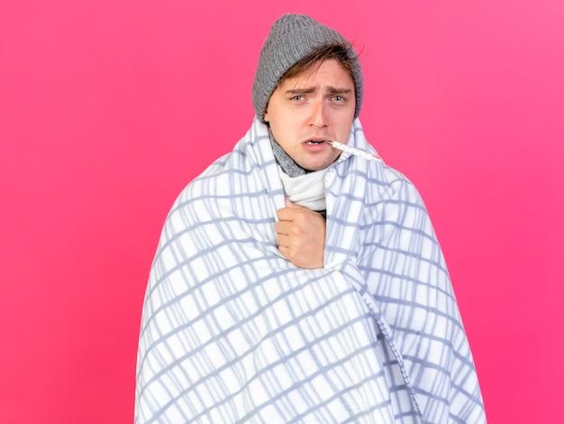 Zwakke jonge knappe blonde zieke man met winter muts en sjaal verpakt in geruite thermometer in mond kijken camera geïsoleerd op crimson achtergrond met kopie ruimte