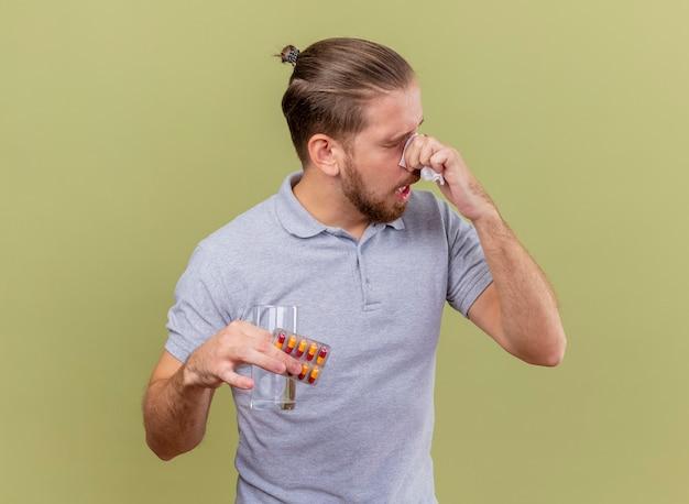Zwakke jonge knappe slavische zieke man met pak capsules glas water en neus afvegen met servet met gesloten ogen geïsoleerd op olijfgroene achtergrond