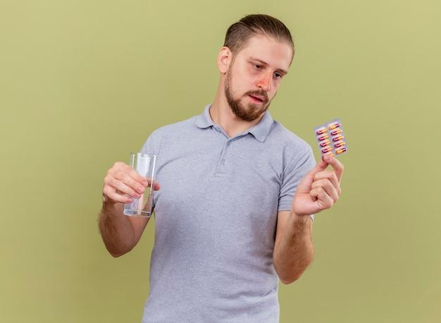 Zwakke jonge knappe slavische zieke man met pakje capsules en glas water kijken naar capsules geïsoleerd op olijfgroene muur met kopie ruimte