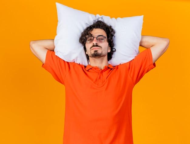 Zwakke jonge zieke man die een bril draagt die hoofdkussen onder hoofd houdt die voorzijde bekijkt die op oranje muur wordt geïsoleerd