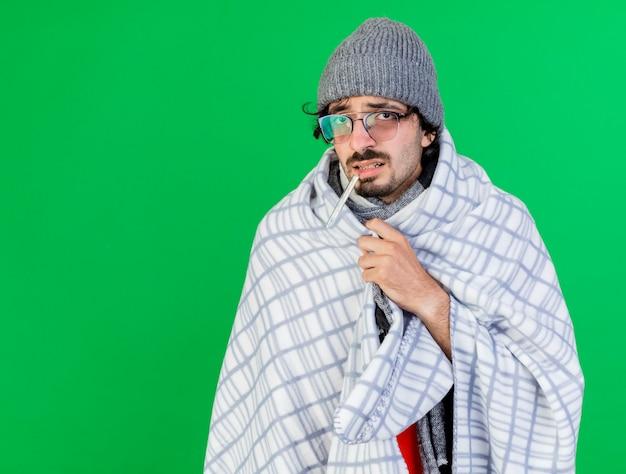 Zwakke jonge zieke man met bril, muts en sjaal gewikkeld in een plaid thermometer in de mond te houden kijkend naar de voorkant grijpende plaid geïsoleerd op groene muur