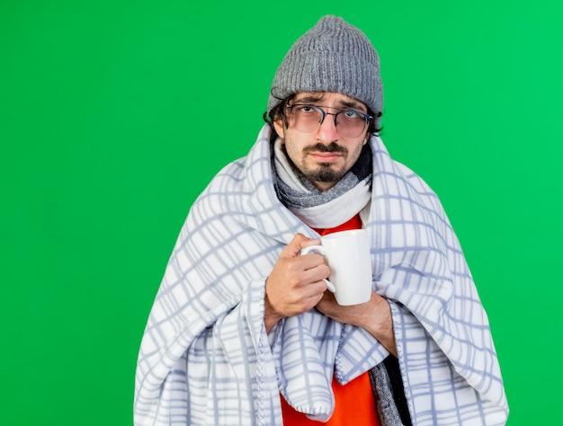 Zwakke jonge zieke man met bril, muts en sjaal gewikkeld in plaid houden kopje thee grijpen plaid kijken voorzijde geïsoleerd op groene muur