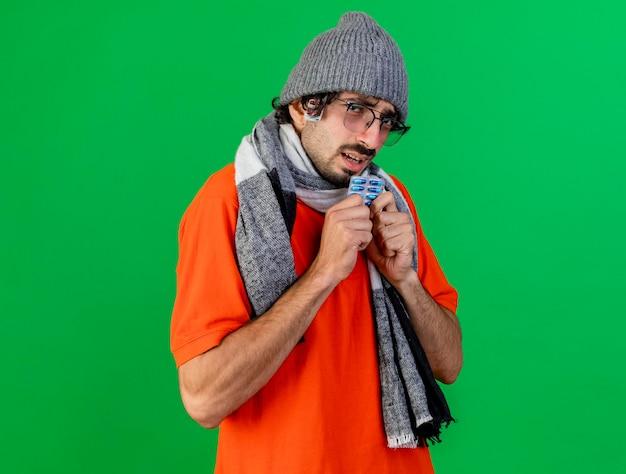 Zwakke jonge zieke man met bril, muts en sjaal houden pak capsules kijken voorkant met pak capsules onder hoed geïsoleerd op groene muur met kopie ruimte
