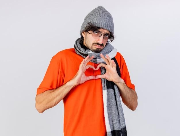 Zwakke jonge zieke man met bril, muts en sjaal kijken naar voorkant hart teken geïsoleerd op een witte muur te doen